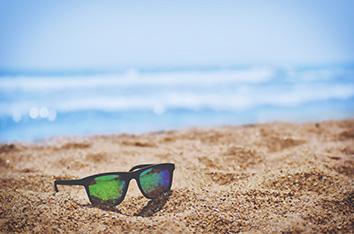 Vacances et voyages, lunettes de soleil sur une plage au bord de l'océan